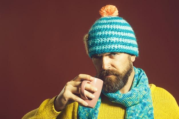 Portret van een knappe, bebaarde man met een trui, sjaal en muts, gekleed in warme winterkleding en