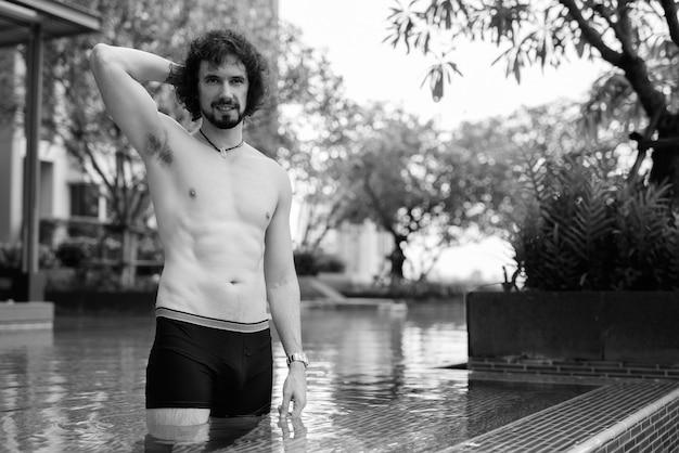 Portret van een knappe bebaarde man met krullend haar zonder shirt ontspannen naast het zwembad swimming