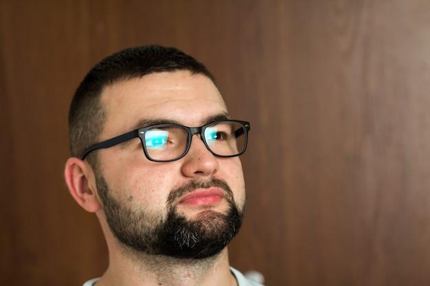 Portret van een knappe, bebaarde, zwartharige intelligente moderne jongeman in een bril met kort kapsel en vriendelijke zwarte ogen die lacht op een onscherpe achtergrond. jeugd en vertrouwen concept.