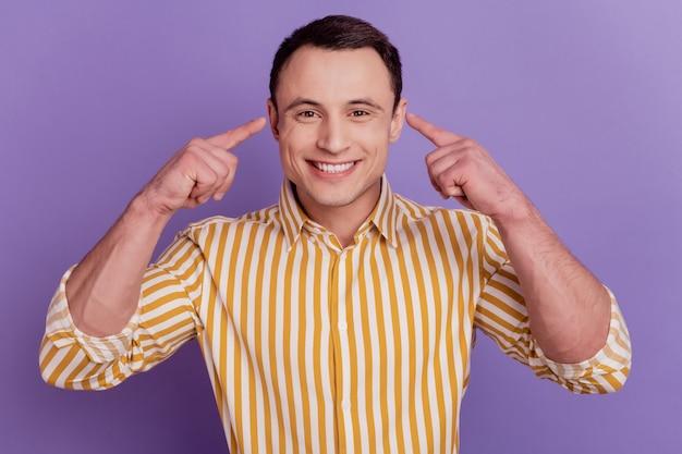 Portret van een knappe, betrouwbare promotor-man geeft aan dat wijsvingers ogen glanzende glimlach op paarse achtergrond hebben