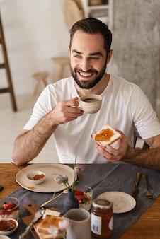 Portret van een knappe brunette man die smartphone gebruikt tijdens het ontbijt in een stijlvolle keuken thuis