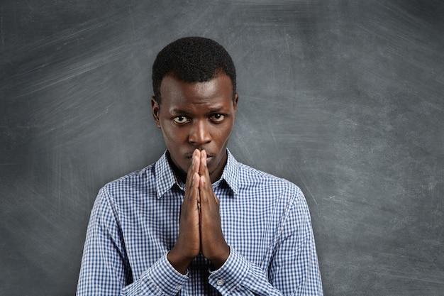 Portret van een knappe, donkere student die hand in hand in gebed, bezorgd en ongeduldig kijkt, de resultaten van eindexamen verwacht of de leraar smeekt om hem nog een kans te geven.