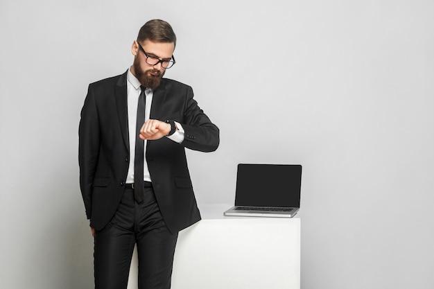 Portret van een knappe, doordachte, bebaarde jonge zakenman in bedrijfsformaat in zwart pak staat en controleert de tijd op zijn eigen handhorloge. geïsoleerd, studio-opname, binnen, grijze achtergrond