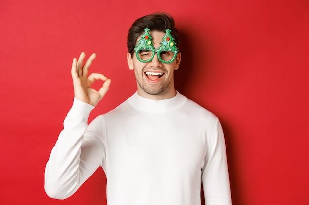 Portret van een knappe en brutale man, met een feestbril en een witte trui, een goed teken en een knipoog, een gelukkig nieuwjaar wensend, staande op een rode achtergrond.