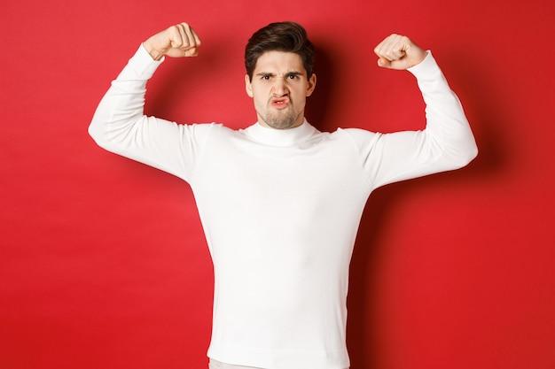 Portret van een knappe en grappige kerel in een witte trui met flex-biceps en een aangemoedigde blik met sterke...