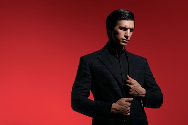 Portret van een knappe ernstige jonge man in zwart pak close-up op rode donkere achtergrond. horizontale weergave.