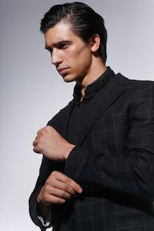 Portret van een knappe ernstige jonge man in zwart pak over wit donker close-up.