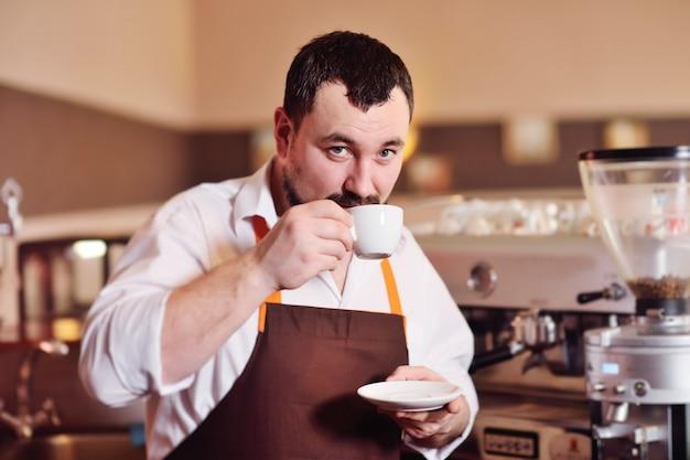 Portret van een knappe gebaarde barista die koffie voorbereidt