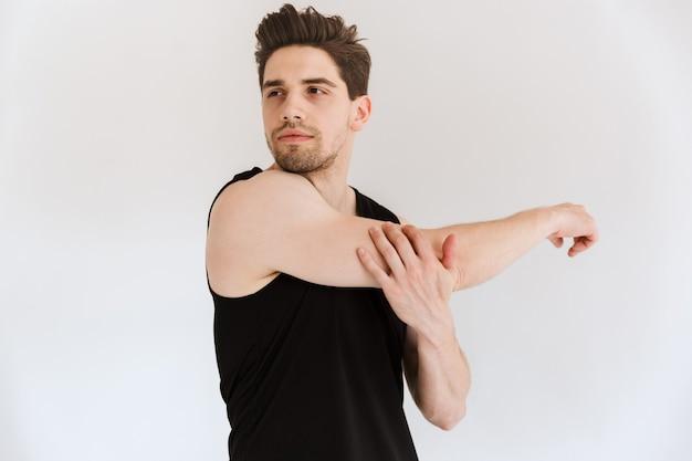 Portret van een knappe, geconcentreerde jonge sportman die over een witte muur wordt geïsoleerd, maakt rekoefeningen.