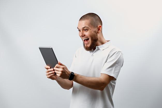 Portret van een knappe gelukkig bebaarde man in een wit t-shirt met een tablet op wit