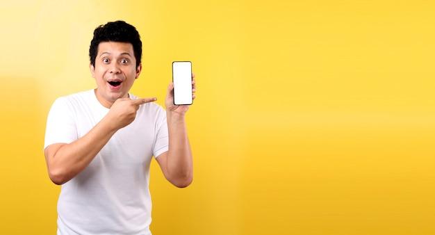 Portret van een knappe, gelukkige glimlachende jonge aziatische mens die mobiele telefoon met een andere geïsoleerde open hand tonen