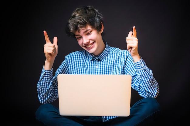 Portret van een knappe, gelukkige jonge man die op de vloer zit en een laptop gebruikt en een geruit hemd en een broek draagt