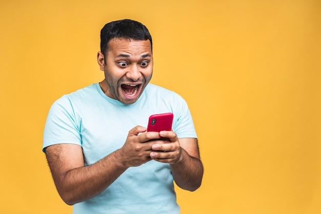 Portret van een knappe, geschokte, verbaasde indiase afro-amerikaanse man die casual berichten verzendt en ontvangt die over gele achtergrond worden geïsoleerd. telefoon gebruiken.