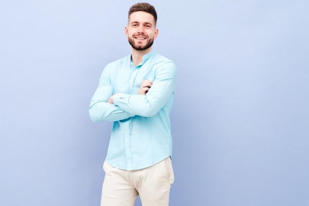 Portret van een knappe glimlachende jonge man met een casual shirt en broek
