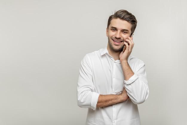 Portret van een knappe glimlachende jongeman in een wit overhemd die op een mobiele telefoon praat en naar de camera kijkt