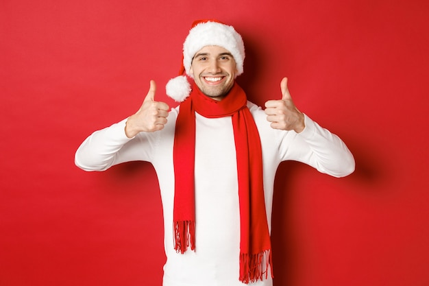 Portret van een knappe glimlachende man in een kerstsjaal en muts met thumbsup die de kerststand viert...