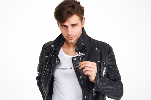 Portret van een knappe glimlachende man in een leren jas poseren
