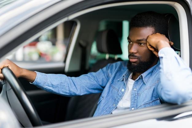 Portret van een knappe glimlachende man stop in een verkeersopstopping die zijn auto bestuurt