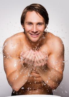 Portret van een knappe glimlachende mens die zijn gezond gezicht met water op grijze muur wast.