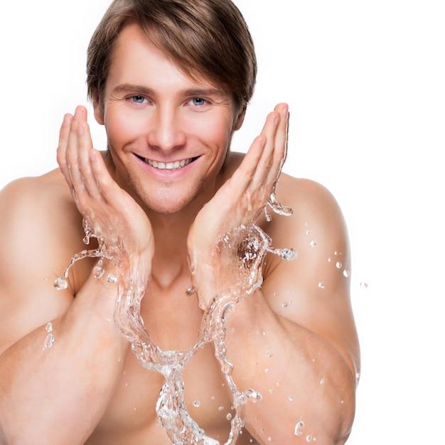 Portret van een knappe glimlachende mens die zijn gezond gezicht met water wast - dat op wit wordt geïsoleerd.