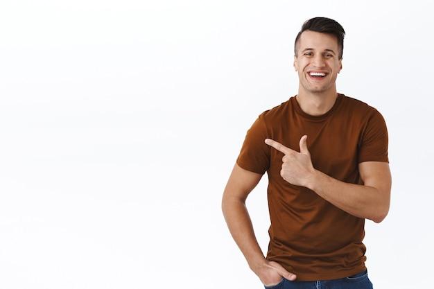 Portret van een knappe glimlachende, vrolijke man die een grafiek of product laat zien, met de vinger naar links wijzend, aan te bevelen klik op de link