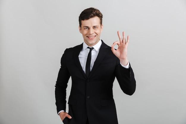 Portret van een knappe glimlachende zelfverzekerde zakenman die een pak draagt dat geïsoleerd staat en ok toont