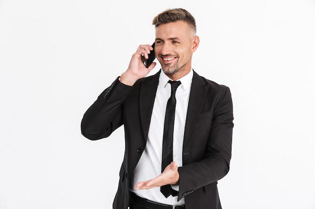 Portret van een knappe glimlachende zelfverzekerde zakenman die een pak draagt dat geïsoleerd staat, op zijn mobiele telefoon praat en wegwijst