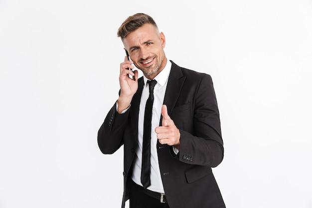 Portret van een knappe glimlachende zelfverzekerde zakenman die een pak draagt dat geïsoleerd staat, praat op een mobiele telefoon en naar voren wijst