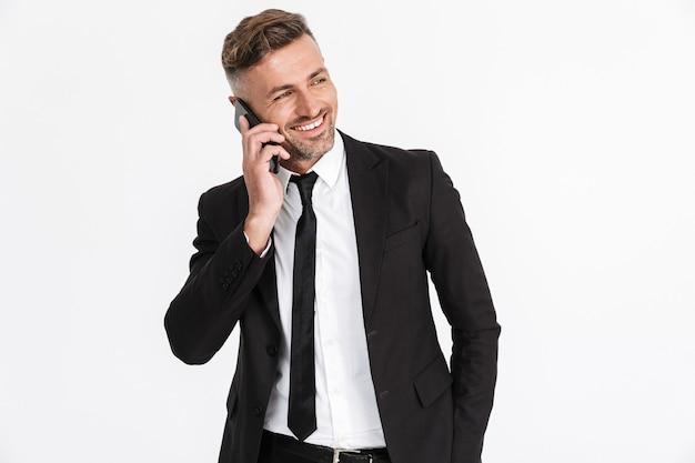 Portret van een knappe glimlachende zelfverzekerde zakenman die een pak draagt dat geïsoleerd staat, pratend op een mobiele telefoon