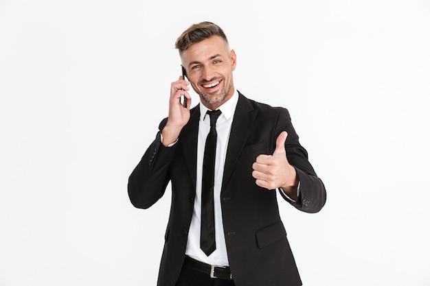 Portret van een knappe glimlachende zelfverzekerde zakenman die een pak draagt dat geïsoleerd staat, pratend op mobiele telefoon, duimen omhoog