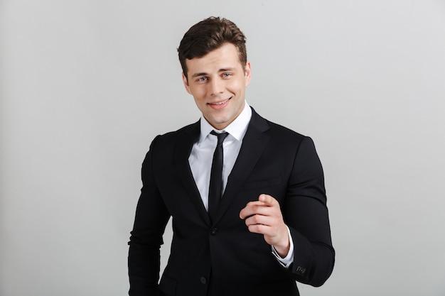 Portret van een knappe glimlachende zelfverzekerde zakenman die een pak draagt dat geïsoleerd staat