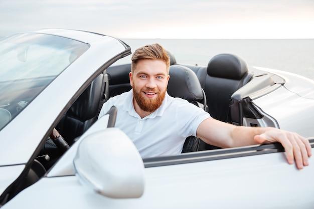 Portret van een knappe jonge, bebaarde man die in zijn auto stapt