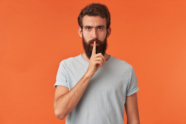 Portret van een knappe jonge, bebaarde man met bruine ogen in een wit t-shirt met een vinger naar de mond, kijkend naar je emotie, attente stilte en zelfverzekerd