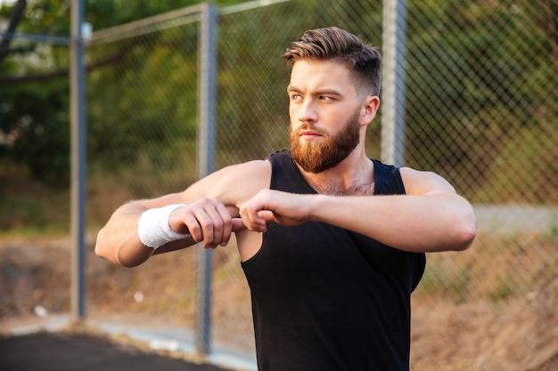 Portret van een knappe jonge, bebaarde sportman die zijn handen uitrekt tijdens het sporten in de buitenlucht