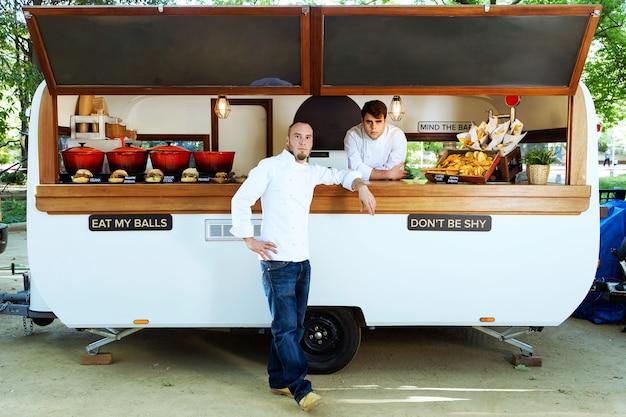 Portret van een knappe jonge chef-kok die naar de camera kijkt en lacht in een foodtruck.