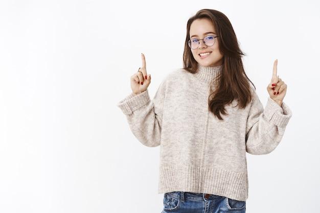 Portret van een knappe jonge en zelfverzekerde vrouw met een bril en een warme trui die handen opsteekt, glimlachend en bijtend op de onderlip van verrukking en verlangen, gretig probeer het product zelf over de grijze muur.