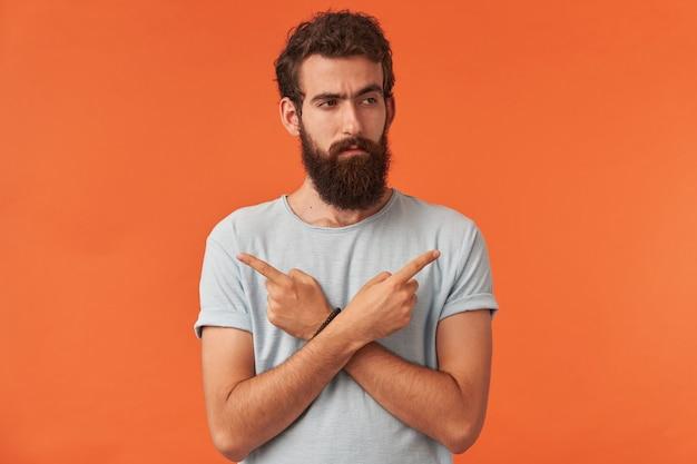 Portret van een knappe jonge kerel met bruine ogen die witte t-shirt vrijetijdskleding draagt, wijst met de vingers opzij emotie attent en zelfverzekerd kijkend opzij staand tegen de rode muur