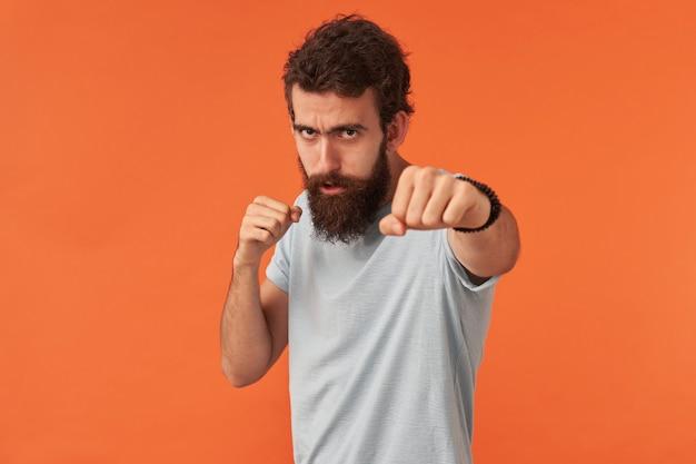Portret van een knappe jonge kerel met een baard die zich voordeed tegen een rode muur met armen in vuisten, een zelfverzekerde vechtersbokser