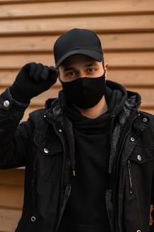 Portret van een knappe jonge kerel met een beschermend medisch masker in een zwarte jas met een hoodie zet zijn pet recht op een houten achtergrond