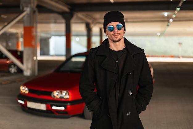 Portret van een knappe jonge kerelbestuurder met zonnebril in een modieuze jas met een hoed in de buurt van een rode auto op een parkeerplaats