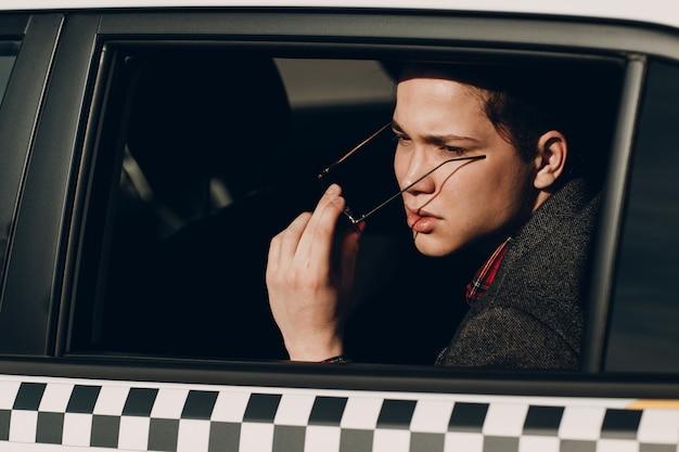 Portret van een knappe jonge man die op de achterbank van een taxi rijdt