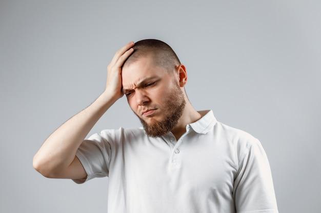 Portret van een knappe jonge man die zijn hoofd in een wit t-shirt op grijs. pijn