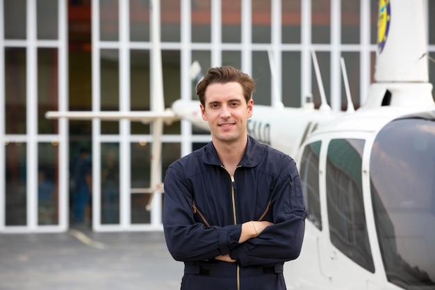 Portret van een knappe jonge man in technicus ingenieur uniforme gebaar tegen luchthaven