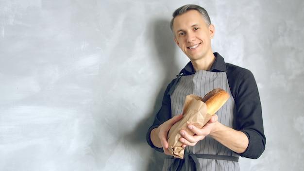 Portret van een knappe jonge man in uniform met verse heerlijke baguettes tegen een grijze achtergrond.