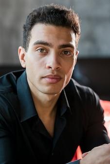 Portret van een knappe jonge man kijkt naar de camera