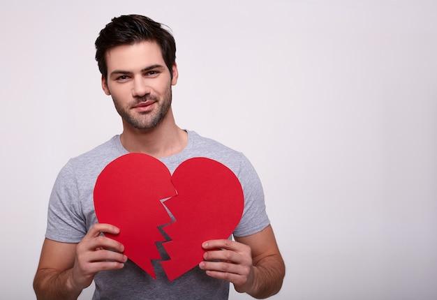 Portret van een knappe jonge man met een gebroken hart in zijn handen.
