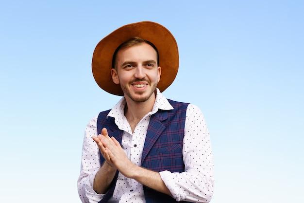 Portret van een knappe jonge man met een hoed tegen een blauwe hemel, een blanke man met een sik die lacht...