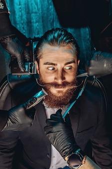 Portret van een knappe jonge man met een snor en baard in een kapperszaak en op zoek met verbazing.