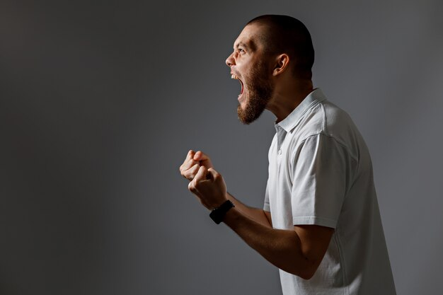 Portret van een knappe jonge man schreeuwen, boos op grijs