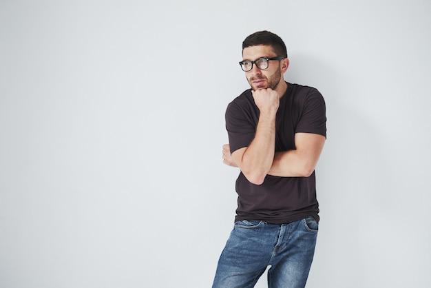 Portret van een knappe jonge mens die op iets denkt, dat op wit wordt geïsoleerd